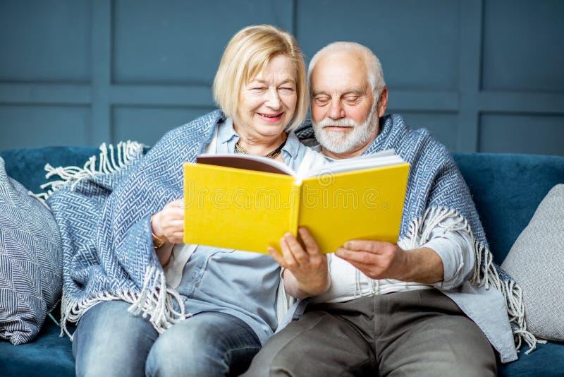 Libro di lettura senior delle coppie sullo strato a casa immagini stock