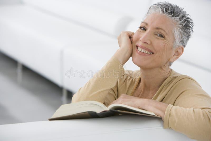 Libro di lettura senior sorridente della donna sul sofà fotografie stock