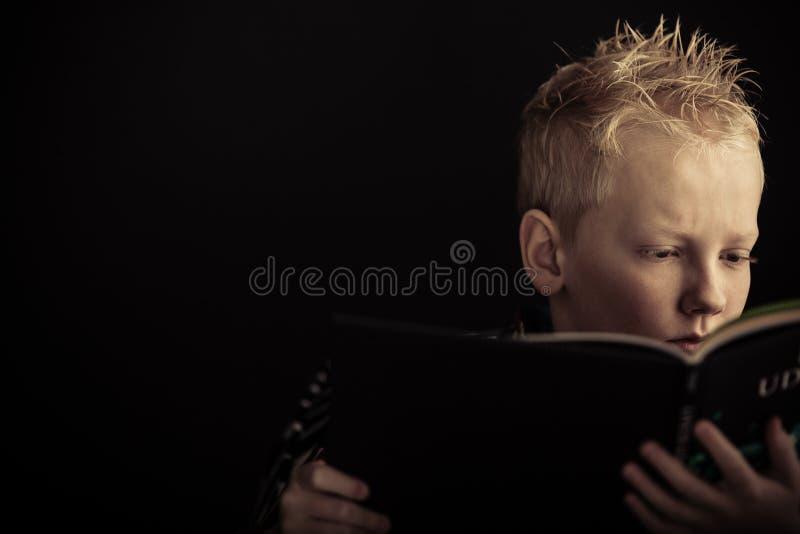 Libro di lettura serio del ragazzo fotografia stock libera da diritti