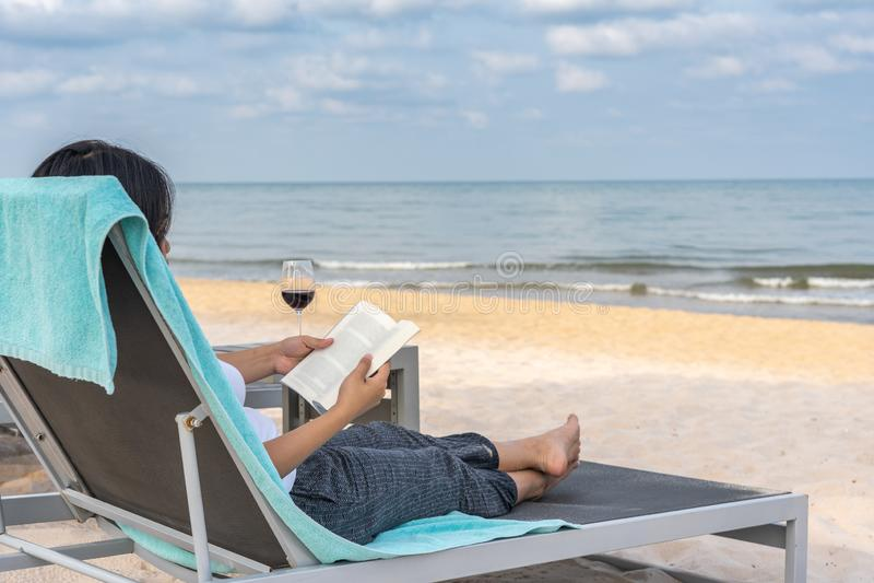 Libro di lettura di signora e rilassarsi sulla spiaggia di estate fotografia stock libera da diritti