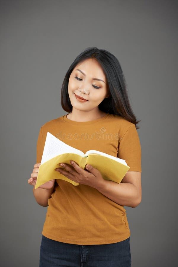 Libro di lettura sorridente della donna fotografia stock libera da diritti