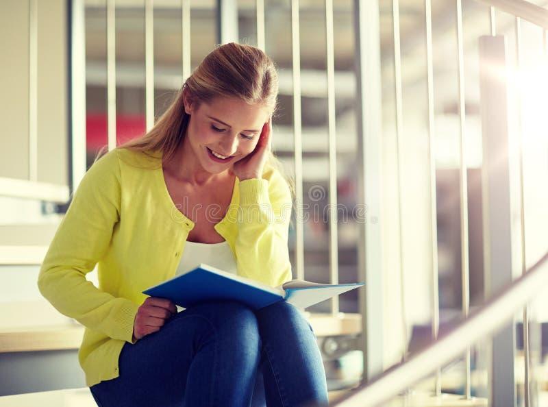 Libro di lettura sorridente della ragazza dello studente della High School immagine stock libera da diritti