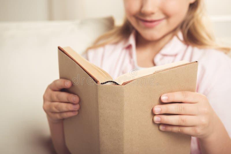 Libro di lettura sorridente della scolara mentre sedendosi sul sofà a casa immagini stock libere da diritti