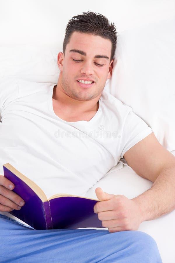 Libro di lettura splendido dell'uomo a letto che sorride immagine stock libera da diritti