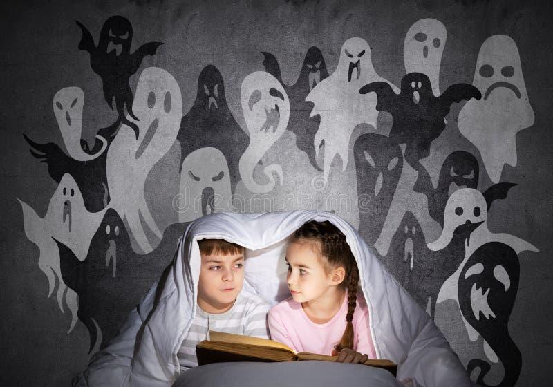 Libro di lettura sveglio del ragazzo e della ragazza a letto fotografia stock