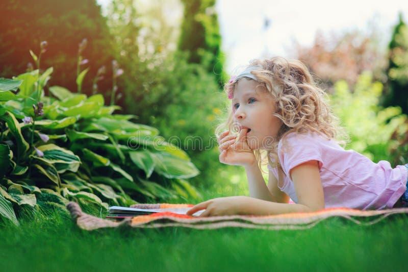 Libro di lettura sveglio della ragazza del bambino nel giardino di estate all'aperto fotografia stock libera da diritti