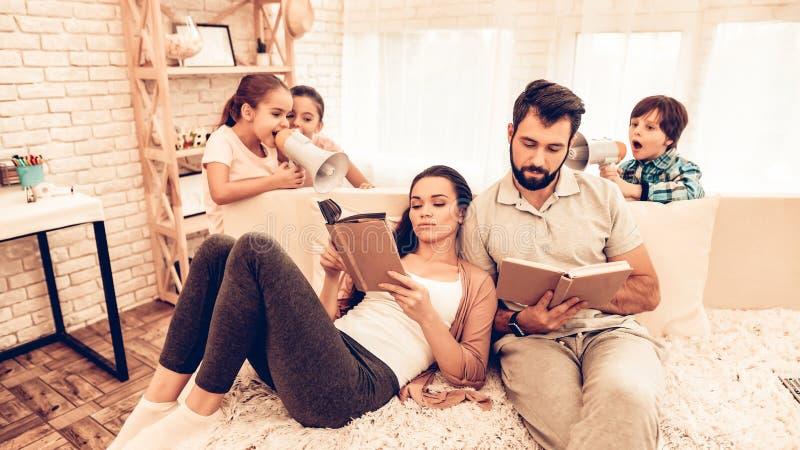 Libro di lettura sveglio felice dei genitori mentre gioco dei bambini fotografia stock