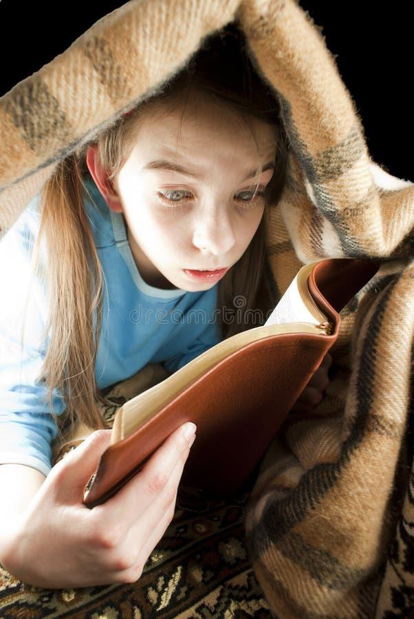 Libro di lettura teenager della ragazza sotto la coperta fotografia stock