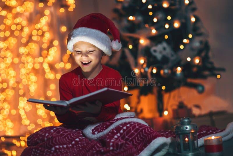 Libro di Natale magico sorpreso di apertura del bambino immagine stock