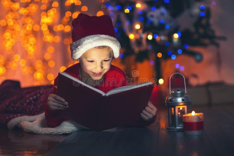Libro di Natale magico sorpreso di apertura del bambino fotografia stock
