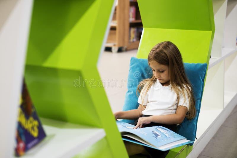 Libro di storia dei bambini della lettura della ragazza in biblioteca immagine stock libera da diritti