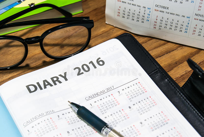Libro diario del planificador en caja de cuero negra con los vidrios y la pluma fotografía de archivo libre de regalías