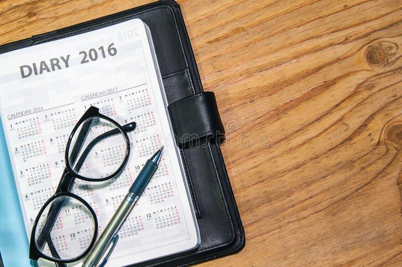 Libro diario del planificador en caja de cuero negra con los vidrios y la pluma imagen de archivo libre de regalías