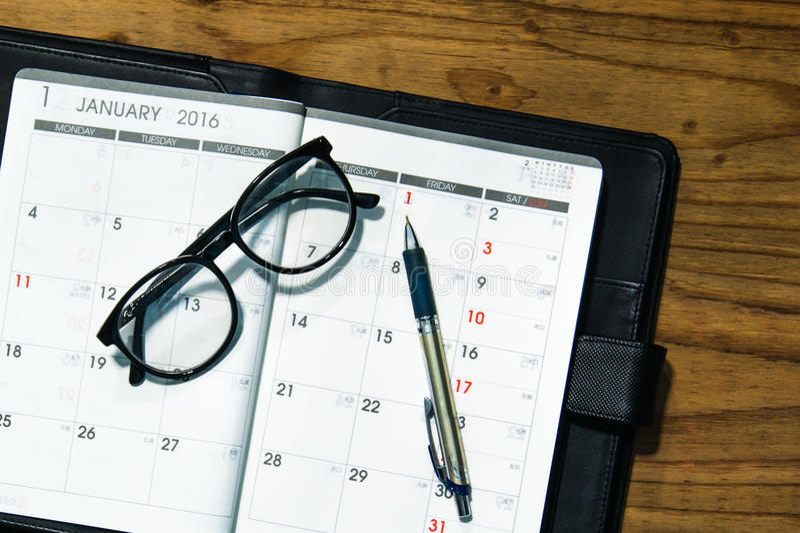 Libro diario del planificador en caja de cuero negra con los vidrios y la pluma encendido foto de archivo libre de regalías