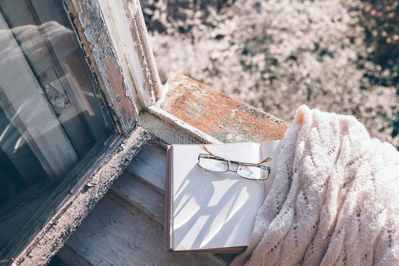 Libro e caffè sul davanzale della finestra sopra l'albero della molla fotografia stock