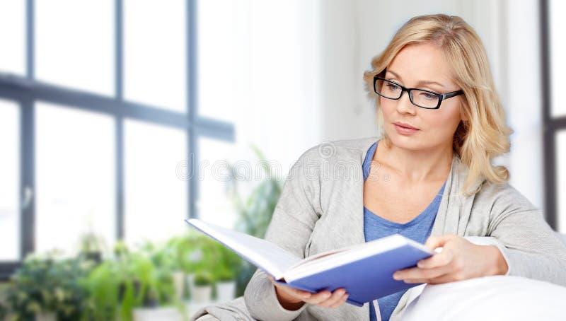Libro e seduta di lettura della donna sullo strato immagini stock libere da diritti
