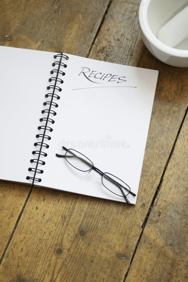 Libro e vetri di ricetta fotografia stock