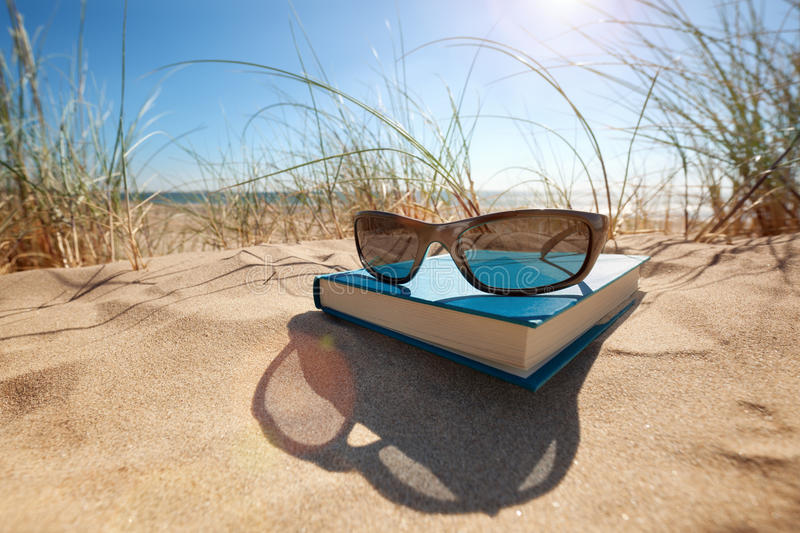 Libro ed occhiali da sole sulla spiaggia immagine stock