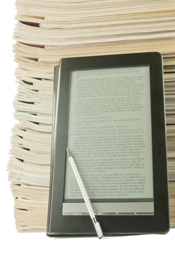 Libro electrónico con una pila de periódicos viejos imágenes de archivo libres de regalías