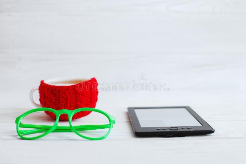 Libro elettronico, vetri e una tazza rossa di tè su un fondo bianco E fotografia stock