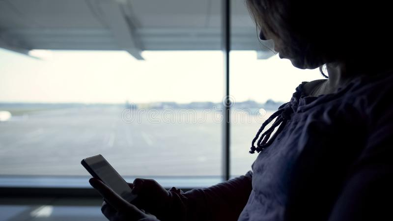 Libro en línea de la lectura turística femenina, para vuelo que espera, pasando tiempo en aeropuerto imagen de archivo libre de regalías