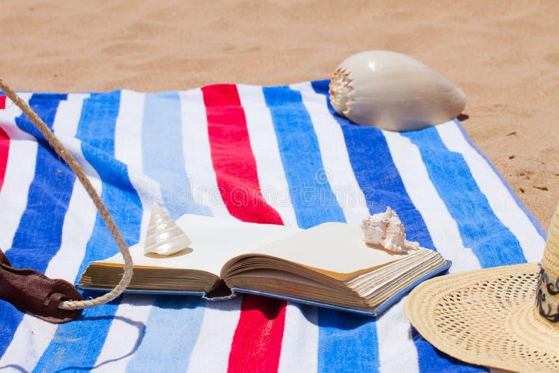 Libro en la toalla de playa imágenes de archivo libres de regalías
