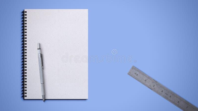 Libro espiral con la pluma y regla en fondo azul foto de archivo