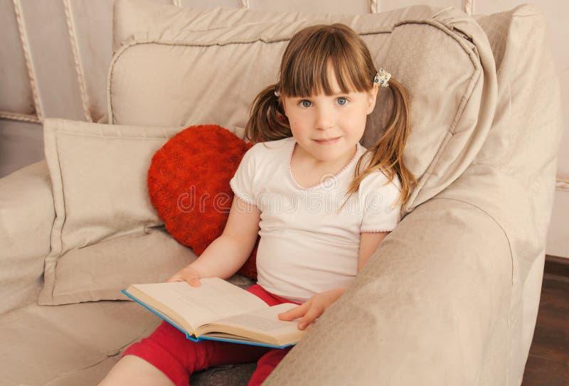 Libro feliz de la pizca de la niña en las manos fotografía de archivo libre de regalías
