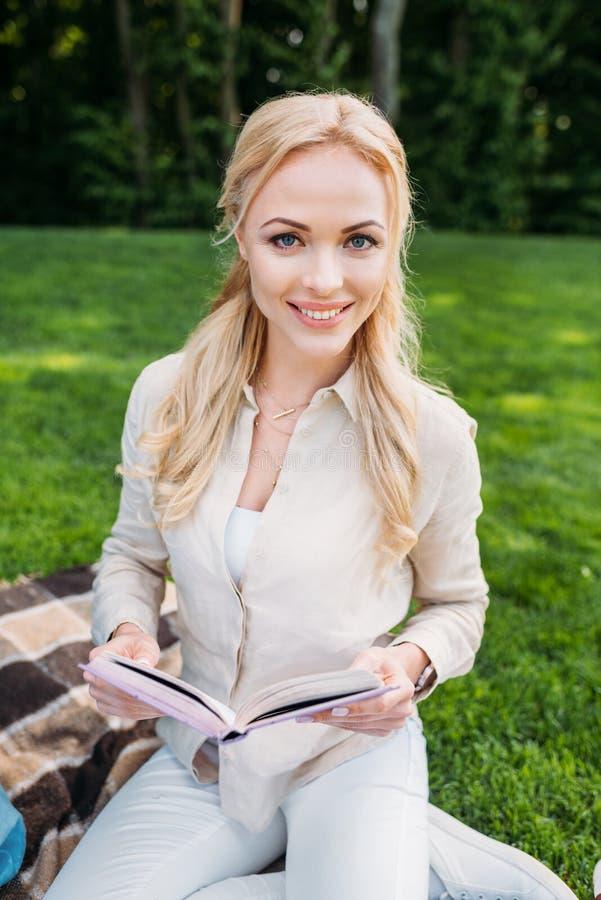 libro feliz de la tenencia de la mujer joven y sonrisa en la cámara mientras que se sienta en la tela escocesa imagenes de archivo