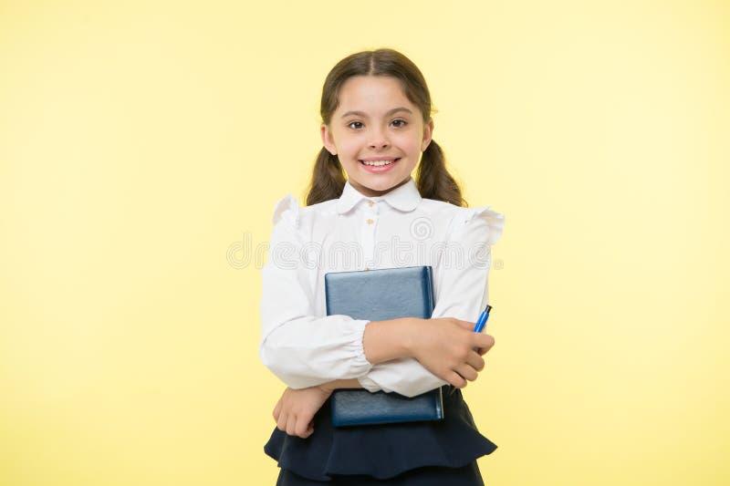 Libro feliz del control de la colegiala en fondo amarillo Sonrisa de la niña con el libro de texto y la pluma Confiado en su cono imágenes de archivo libres de regalías