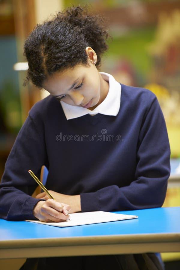 Libro femenino de la escritura del alumno de la escuela primaria en sala de clase foto de archivo libre de regalías