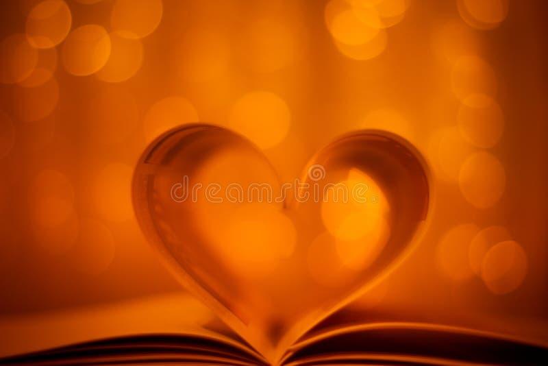 Libro a forma di del cuore sul fondo del bokeh dell'oro immagine stock libera da diritti