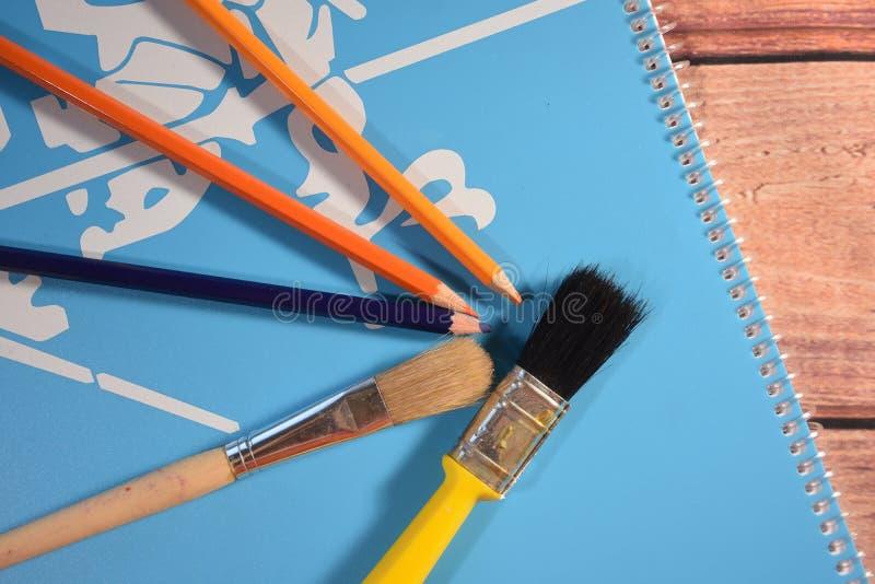 Libro ilustrado, lápices y cepillos foto de archivo