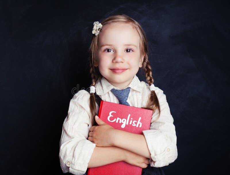 Libro inglés del abarcamiento de la muchacha del pequeño niño contra la pizarra imagen de archivo