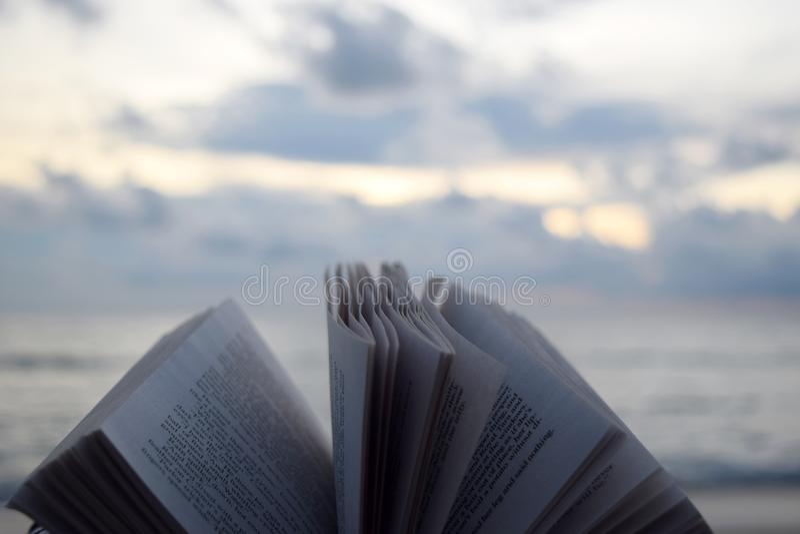 Libro a leer durante día de fiesta de la playa foto de archivo