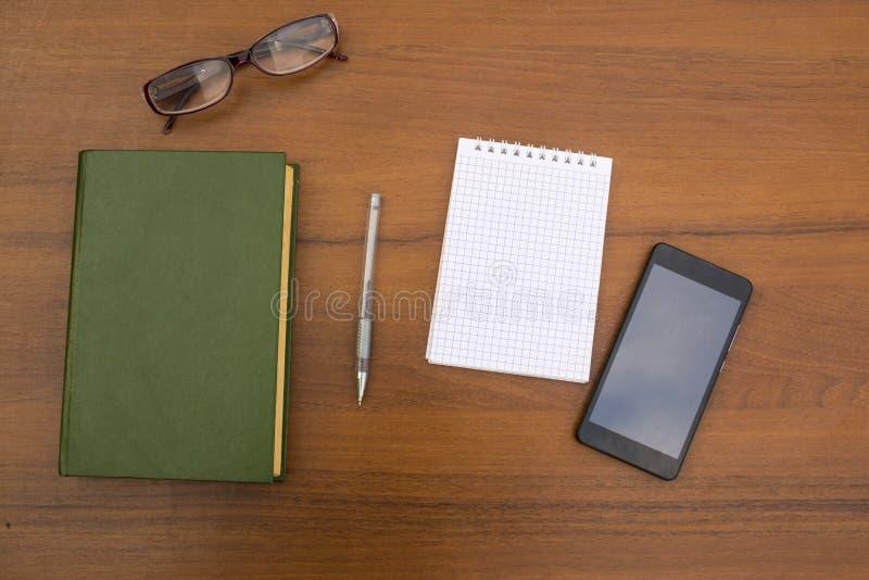 Libro, libreta, pluma, lentes y teléfono elegante en el escritorio de madera imagenes de archivo