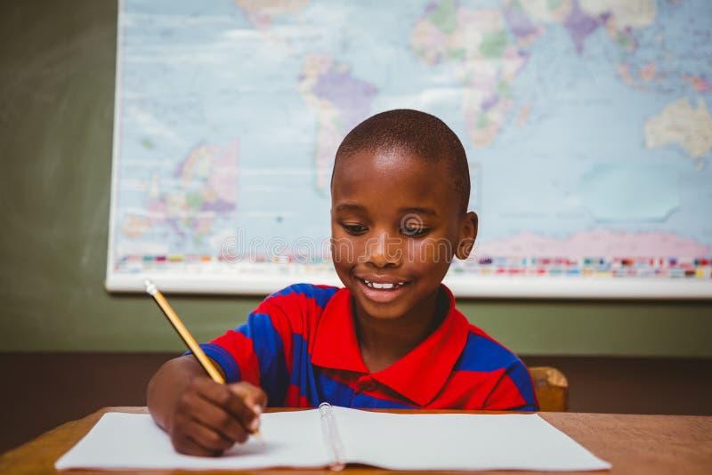 Libro lindo de la escritura del niño pequeño en sala de clase fotos de archivo