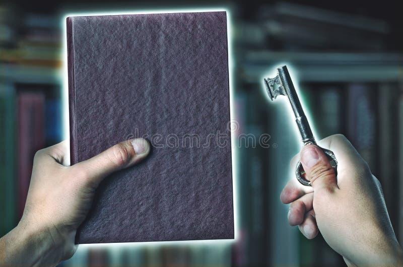 Libro magico e chiave con luce magica fotografie stock