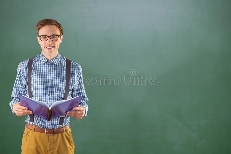 Libro maschio felice della tenuta dello studente di college mentre stando contro la lavagna fotografie stock libere da diritti