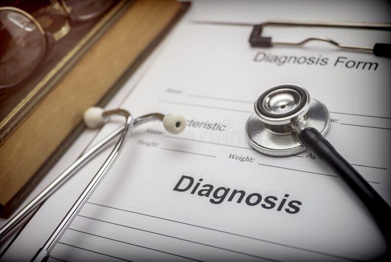 Libro medico con uno stetoscopio e una forma diagnostica fotografia stock libera da diritti