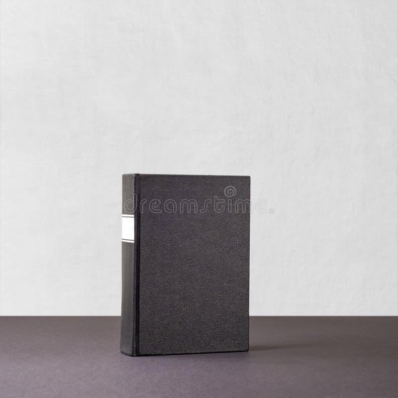 Libro negro con el marco blanco en la espina dorsal que se coloca en superficie oscura fotos de archivo