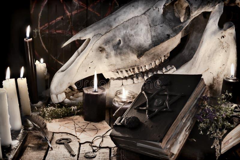 Libro nero con il pentagramma, candele nere e cranio spaventoso del cavallo fotografie stock