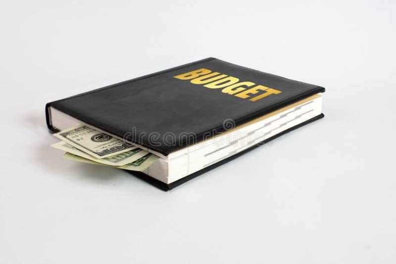 Libro nero con soldi ed il bilancio dell'iscrizione su fondo bianco fotografia stock libera da diritti