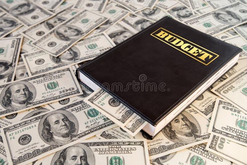 Libro nero con soldi ed il bilancio dell'iscrizione sul fondo delle banconote del dollaro fotografie stock