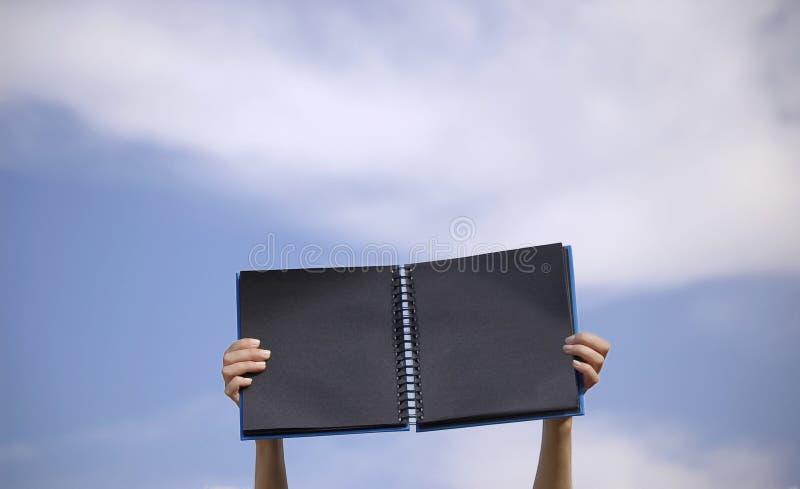 Libro nero in un cielo blu immagini stock libere da diritti