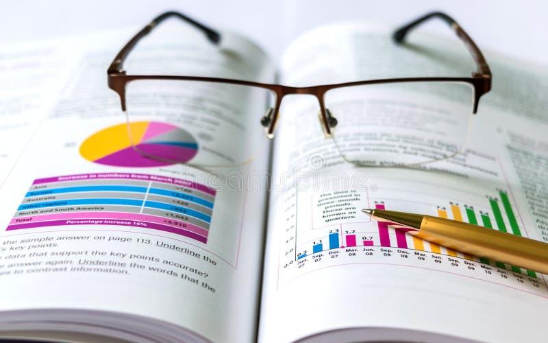 Libro, penna, occhiali e grafici fotografia stock