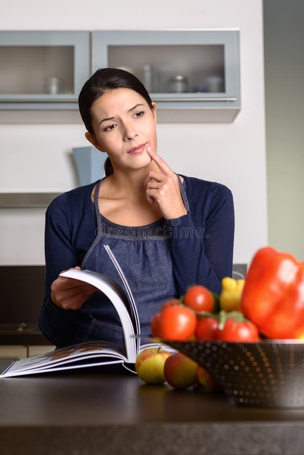 Libro pensativo de la receta de la lectura de la mujer en la encimera foto de archivo