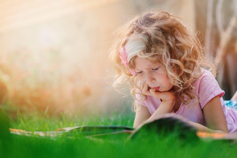 Libro pensativo del aprendizaje y de lectura de la muchacha del niño el vacaciones de verano en el jardín fotografía de archivo libre de regalías