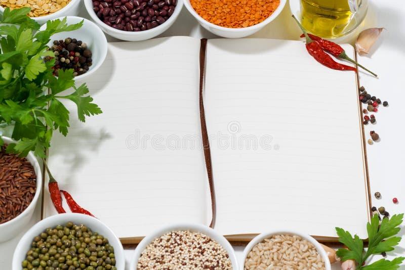Libro per le ricette, le spezie, le erbe e l'assortimento dei legumi, vista superiore immagini stock
