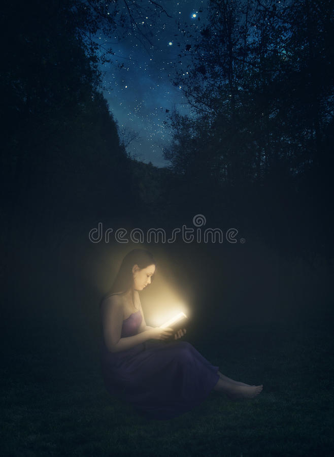 Libro que brilla intensamente en la noche fotos de archivo